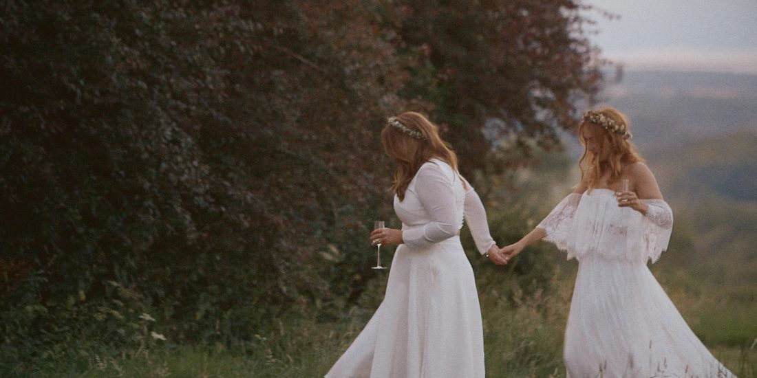 Two brides holding hands in a forest