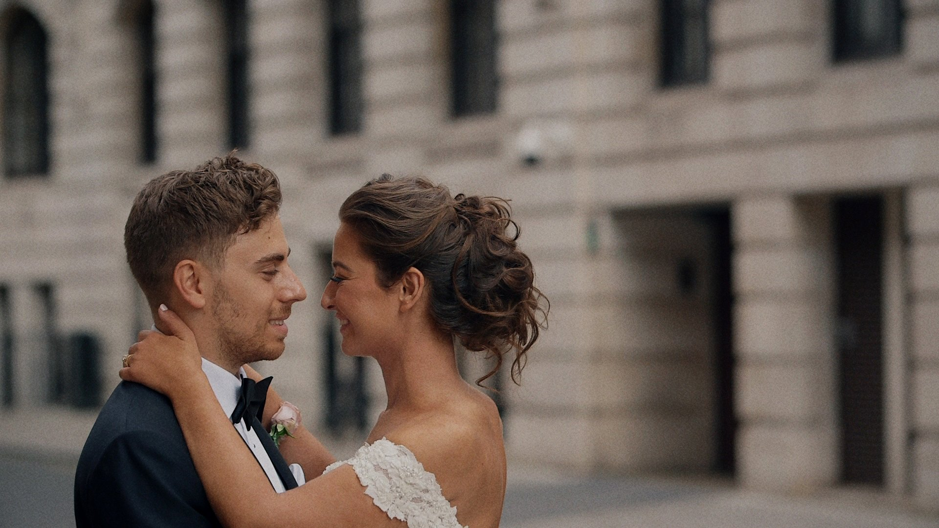 A bride and groom embrace for a kiss outside 8 Northumberland Avenue
