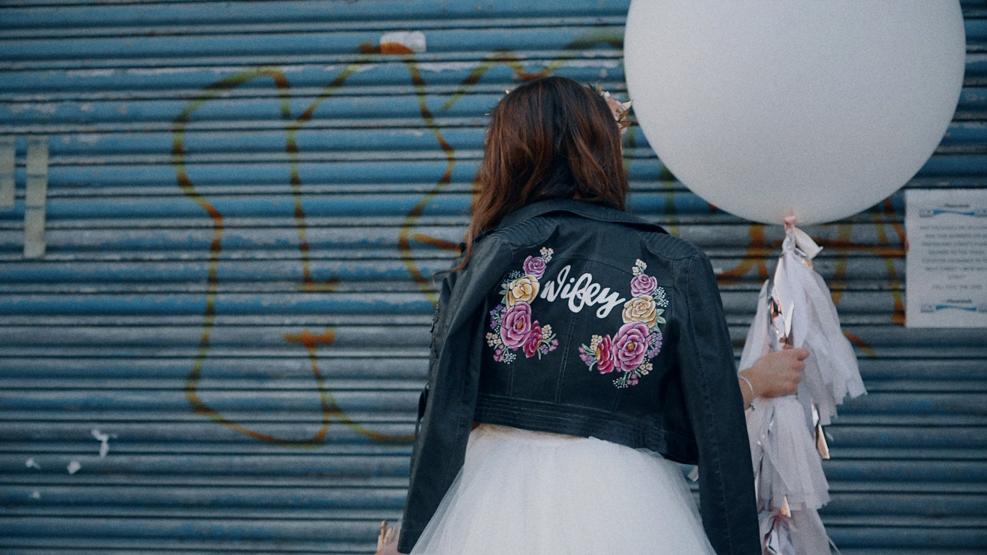 Bride in a leather jacket holding an oversize wedding balloon