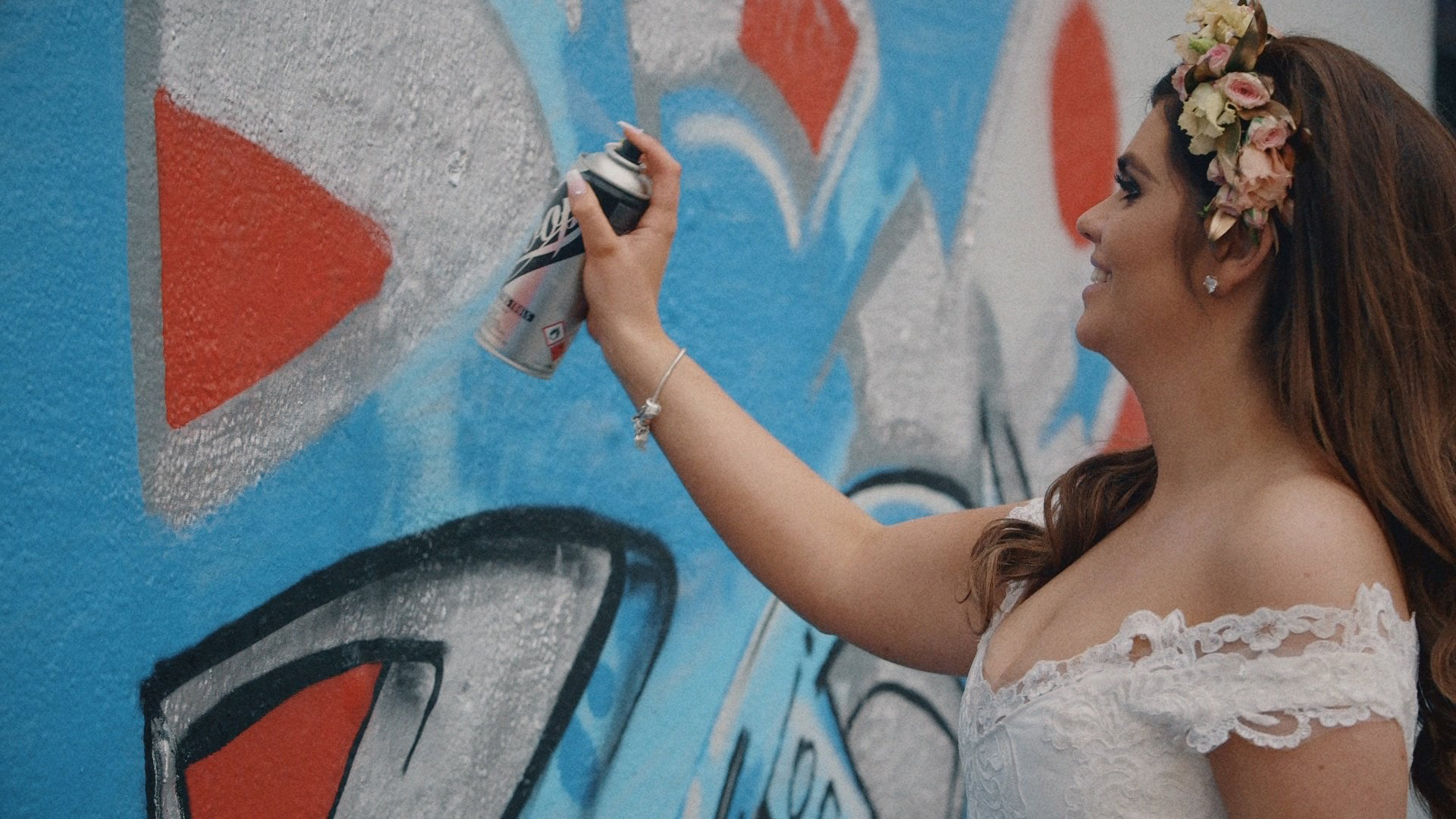 Bride spray painting on a wall in her wedding dress